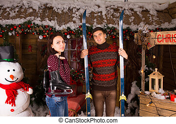 Couple with Skates and Skis in front of Log Cabin