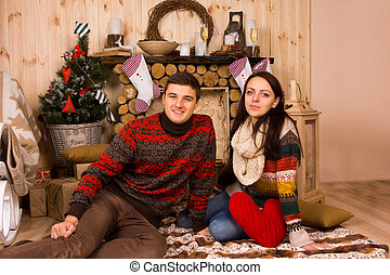 Couple Sitting on Floor inside Log Cabin in Winter