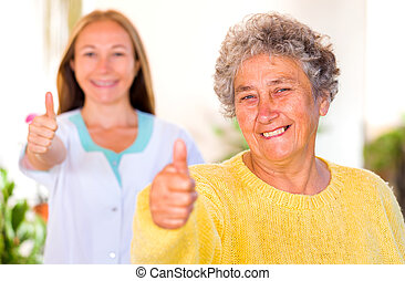 Elderly home care - Happy elderly woman with her caregiver...