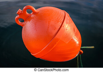 Plastic orange boat buoy floating in the sea