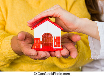 Protect your house - Photo of a toy house protected by hands