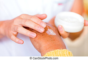 Skin care - The carer rubbing the elderly womans hand with...