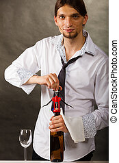 Man opening bottle of wine with corkscrew - Man waiter...