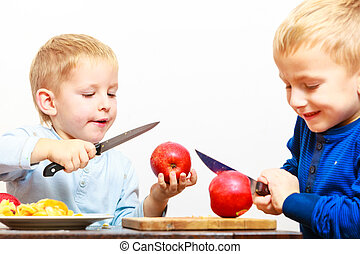 Little boys cutting apple with a kitchen knife - Children...