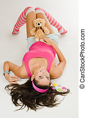 woman lay on white floor in pink clhothes with toy -...