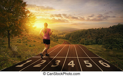 Running on a track - A woman runs on a track through the...