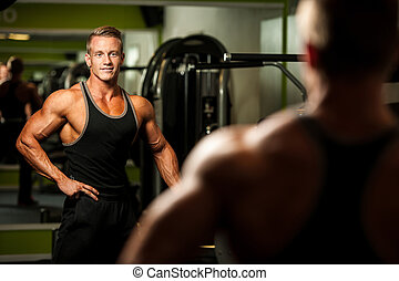 Handsome man looking in mirror after body building workout...