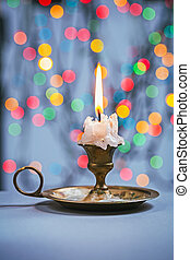 close up view on candle in candlestick on blue table and backgro