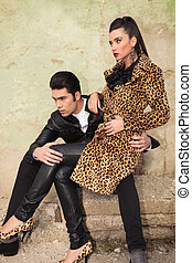 young fashion couple sitting on old factory ruins
