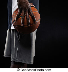 African basketball player holding ball - Cropped image of a...