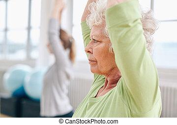 Senior woman practicing yoga at gym - Close-up image of...