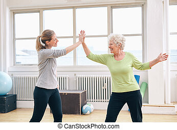 Senior woman giving high five to her coach at gym - Senior...