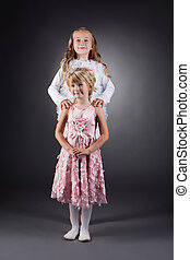 Image of beautiful little sisters posing in studio -...