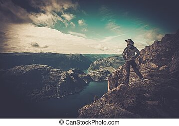 Man hiker looking over fjord panorama