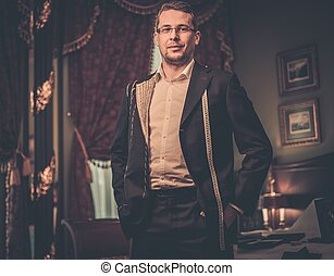 Middle-aged man trying on custom made suit in luxury vintage...