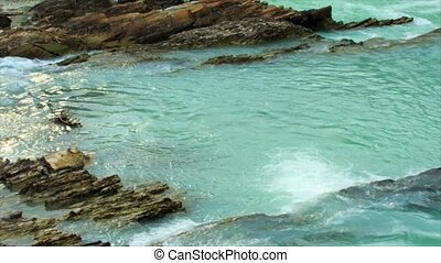 Turquoise water stream - a flow of turquoise water in the...