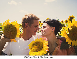 Loving couple in a field of sunflowers