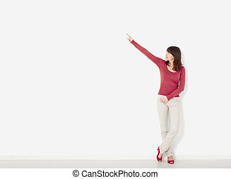 Woman pointing - Beautiful young woman against to a white...