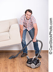 Cleaning - Young smiling man is doing house cleaning with...
