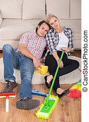Cleaning - Young couple are sitting on the floor with...
