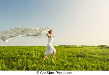 Freedom - Young beautiful woman running while holding a...