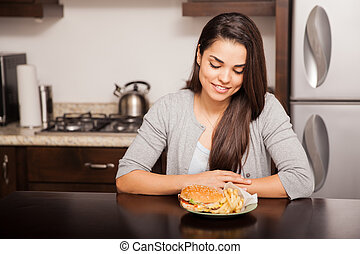 About to eat a delicious burger - Pretty girl looking at a...