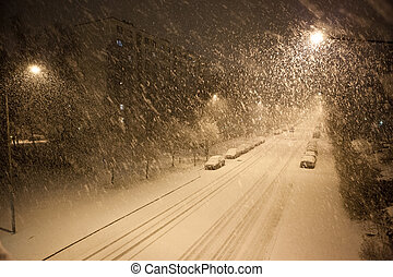 a lot of snowfall and empty road at night in suburb area
