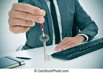 man in an office giving a key - a man in suit sitting in an...