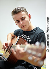 Teenager playing guitar - Closeup of a teenage boy playing...