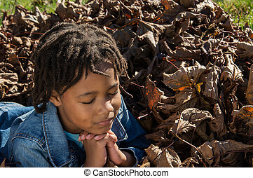 Girl in Prayer - An African American girl praying in a pile...