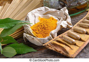 Tumeric powder spice on wooden board with tabletes as...