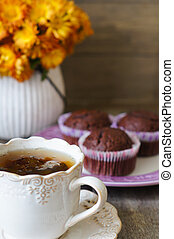 Chocolate cupcakes, cup of tea and flowers on a table