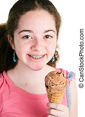 Girl with Braces Eating Ice Cream - Portrait of cute Latina...