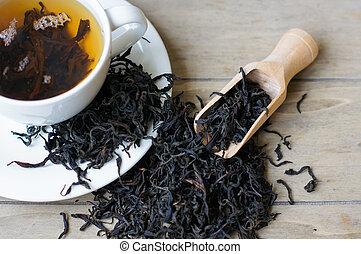 Cup of tea surrouded dry tea leaveas