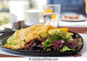 Breakfast with vegetarian omelet on black plate with orange...