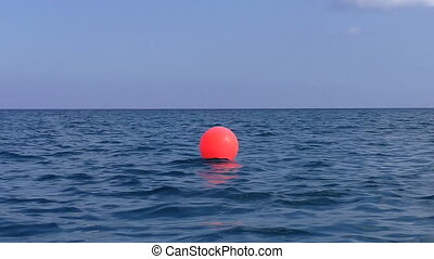 Red buoy in the sea - Low angle panning shot of a red single...