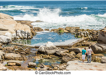 Man Made Tidal Pool - Two people standing on the rocks at...