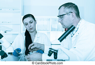 Couple of scientists at work in a laboratory .