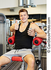 smiling young man with smartphone in gym - sport,...