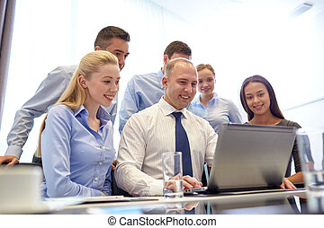 smiling business people with laptop in office - business,...