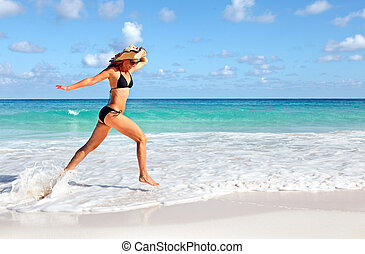 Happy woman running on the beach.