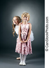 Funny girl posing with her shy little sister - Studio shot...