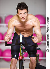 Topless Muscular Man Spinning Gym Bike - Close up Topless...