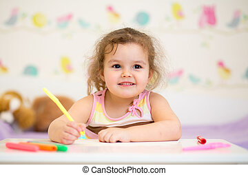 kid girl paints in nursery at home