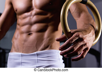 Man body with gymnastic ring close up