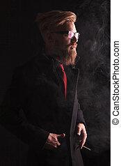 elegant fashion man looking away while smoking - Portrait of...