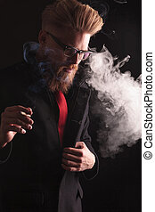 fashion man pulling his coat while smoking - Portrait of a...