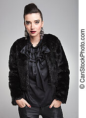 Young fashion woman looking at the camera while holding her...