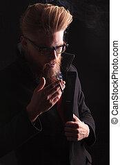 beard man looking down while enjoying his cigarette. - Close...