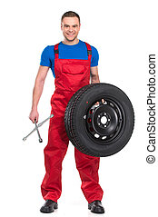 mechanic standing and holding wrench and tire. smiling man...